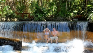 Couple sitting under the waterfall at Tabacon Hot Springs