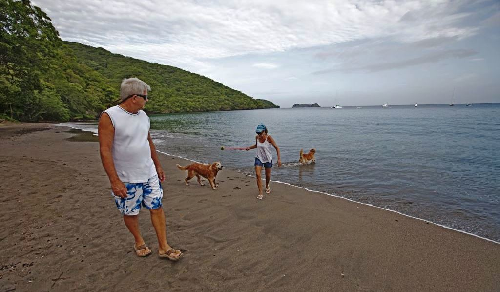 Couple walking on the beach with their dogs in Playa Hermosa